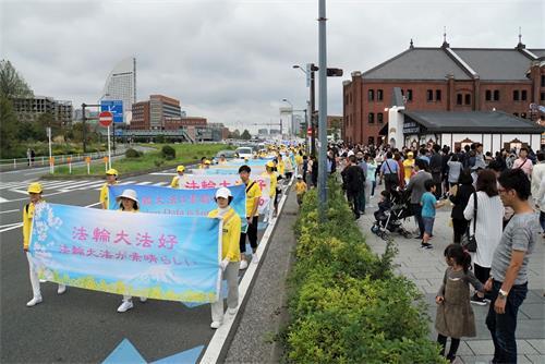 '图6:法轮功学员的游行队伍经过著名景点横滨红砖房,游客纷纷拍照'