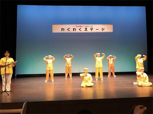 法轮功学员在生涯学习庆典舞台演示法轮功的五套功法动作
