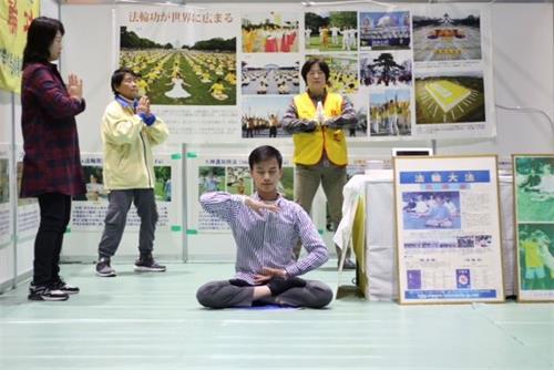 '图5~6:法轮功学员在第22届祖父江银杏黄叶节活动期间,在展位上炼功时'