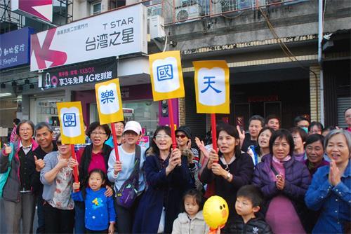 """'图7:一群嘉义市民在民族路上兴奋的举着写着""""天国乐团""""的广告牌欢迎天国乐团。'"""