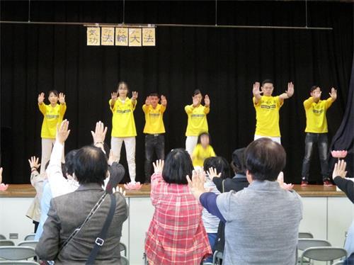 '图1:观众认真的一起和台上的法轮功学员们学炼。'