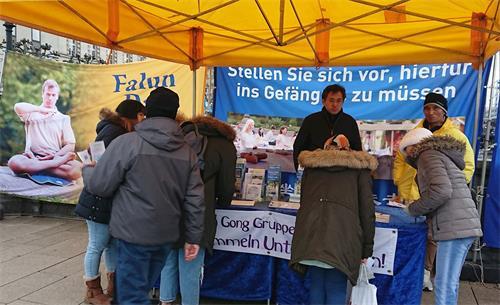 '图1~2:二零一九年十二月七日,法轮功学员在德国汉堡瑞生丹桥设立真相点,民众雨中签名,支持反迫害。'