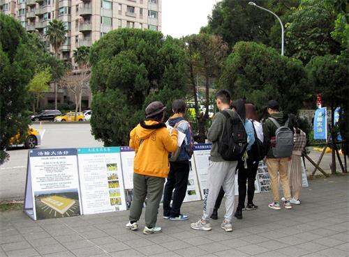 图7~8:大陆游客观看展板内容并聆听法轮功学员讲真相。