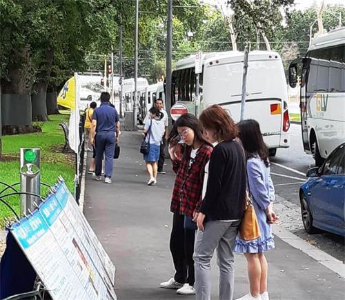墨尔本市中心著名景点费茨罗伊公园是大陆游客了解法轮功真相的窗口。图为中国新年期间,大陆客在阅读摆放在公园入口处的<span class='voca' kid='53'>大法</span>真相展板。