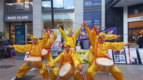 '图4~5:法轮功学员们表演了喜庆的舞狮子和打鼓节目'