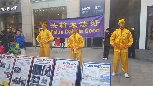 '图6:法轮功学员身着中国传统炼功的服装展示法轮功的五套功法'