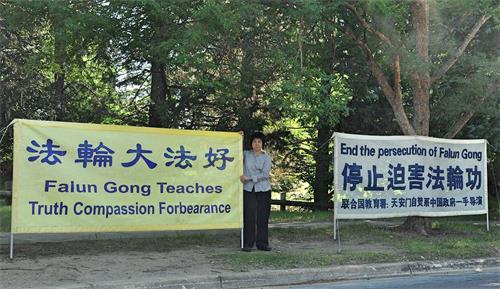'图1:在澳洲首都堪培拉,越南裔法轮功学员金(Kim)常年坚持每天清晨在中领馆对面展开法轮功真相横幅。'