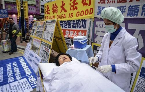 '图:二零一三年一月十二日,法轮功学员在香港的一个购物区模拟中共强摘器官暴行。他们说他们的同修受到酷刑迫害,并被强摘器官。'