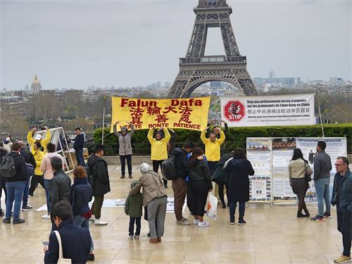 '图1:三月二十四日下午,人权广场人流不断,法轮功学员在巴黎的人权广场进行炼功和讲真相的活动。人们被法轮功学员安静、祥和的炼功吸引,不少游客驻足了解真相。'