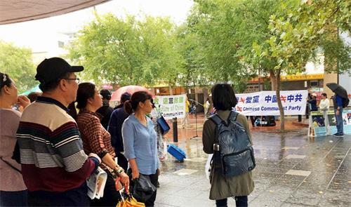'图3:法轮功学员的讲真相活动,吸引了不少华人驻足了解观看,了解真相。'