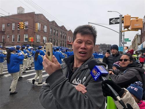 '图12:正在用手机录像的陈先生赞叹天国乐团很棒。'