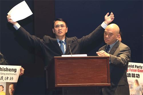 """'图2:法轮功学员于溟在新闻发布会上演示中共监狱的""""吊铐""""酷刑,他曾被这一酷刑持续折磨长达一个月。'"""