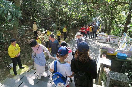 '图1~2:玄光寺的青龙步道上游客如织,法轮功学员布置了真相展板,向游客派送资料,并展示<span class='voca' kid='86'>功法</span>。'