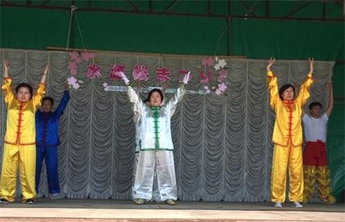 '图5:法轮功学员在丰田市水源公园樱花节的舞台上进行法轮功的功法展示'