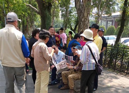 图4:法轮功学员向中国大陆游客讲真相,也是景点上的指路灯、方向塔。