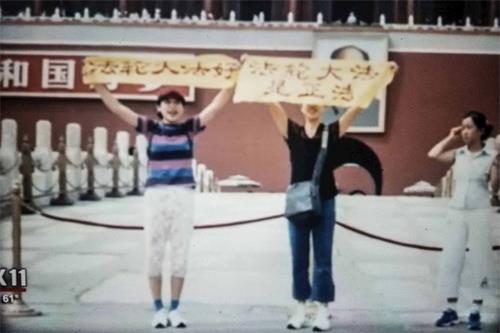 """'图4:二零零一年,王可非和姐姐王易非在天安门广场举着""""法轮大法好""""和""""法轮大法是正法""""的横幅'"""