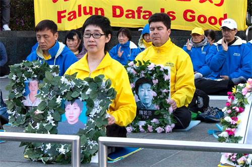 '图7:今年四月二十日,法轮功学员王易非手持被迫害致死的妹妹王可非的遗像'
