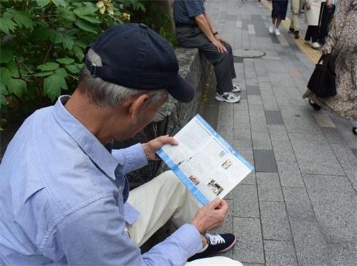 '图4:阅读法轮功真相资料的佐藤'