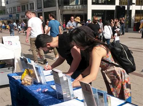 '图5~8:为了帮助制止在中国发生的强摘器官罪行,路人在征签表上签名。'