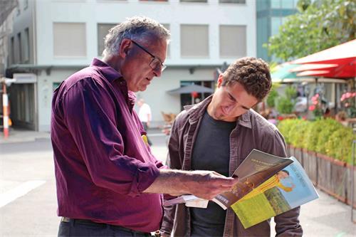 图1~2:这位路人正在跟学员交谈,了解法轮功的真相。