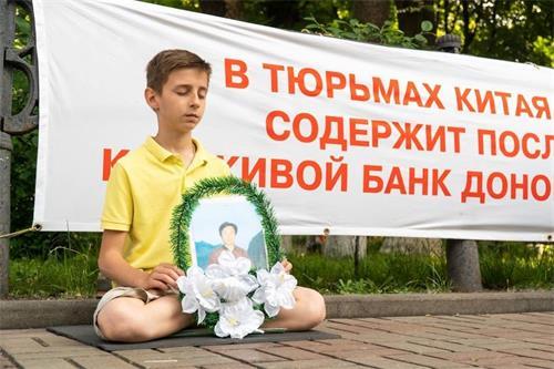 '图1~2:法轮功学员在基辅中使馆前抗议中共迫害'