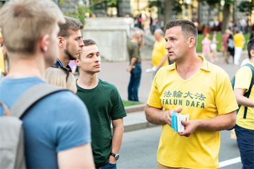 '图9:法轮功学员在基辅市中心向民众讲真相。'