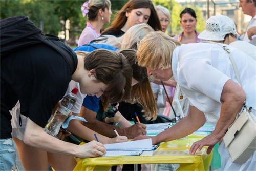 '图10:基辅市中心,民众签名声援法轮功反迫害。'