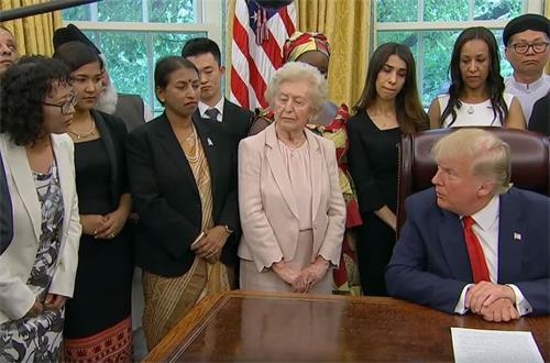 '图1:二零一九年七月十七日下午四点半,美国总统川普在白宫椭圆形办公室会见来自十七个国家的二十七位宗教迫害幸存者,其中包括来自中国江苏省南京市的法轮功学员张玉华女士。图为张玉华女士向川普总统讲述法轮功学员遭受中共迫害的真相。'
