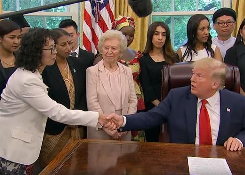 '图2:二零一九年七月十七日下午,美国总统川普在白宫椭圆形办公室会见来自十七个国家的二十七位宗教迫害幸存者。图为川普总统与来自中国的法轮功学员张玉华女士握手。'
