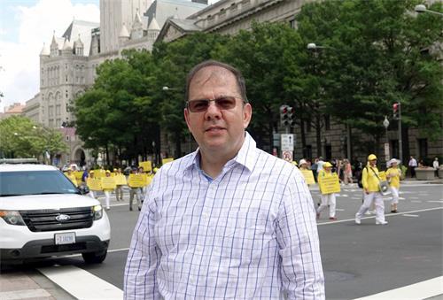'图18:在一个国际组织工作的艾尔第一次听说法轮功,他说这么多人冒着酷暑走在宪法大道上,一定事关重大。'