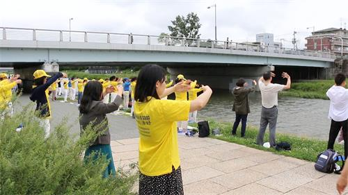 '图1~2:当天早晨九点到十一点,法轮功学员在京都市政府附近的御池大桥(Oike-ohashiBridge)下鸭川河畔的集体炼功,吸引了许多有缘人驻足了解法轮功。'