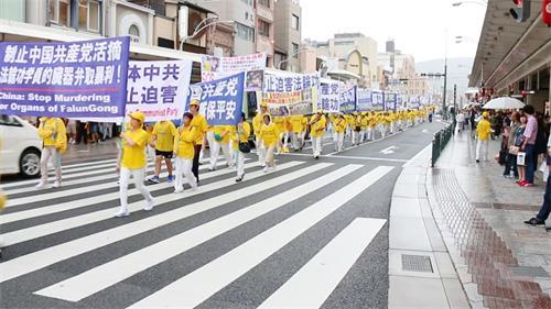 '图3~5:随后,法轮功学员反迫害二十周年游行队伍出现在繁华的京都大街上,引来许多游客驻足观看。'