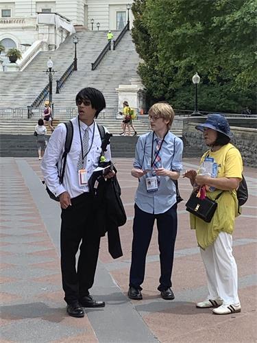图16:两位年轻人一边看着旁边的集会横幅,一边听法轮功学员讲述真相