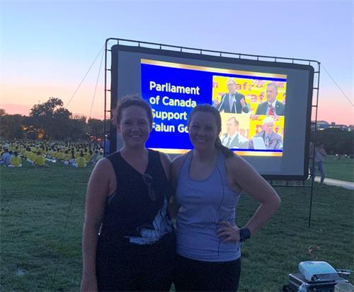 金·司考特(Kim Scott)(右)和瑪麗莎·布朗( Marissa Brown)在法輪功燭光守夜投影圖片前留影