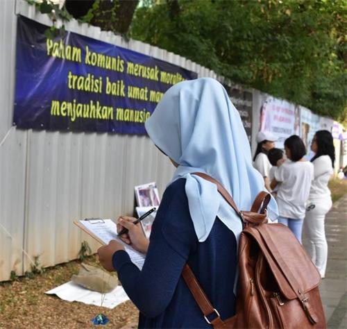 '图4~5:雅加达中使馆前,法轮功学员的真相横幅吸引过往车辆、行人的关注,民众纷纷签名支持反迫害。'