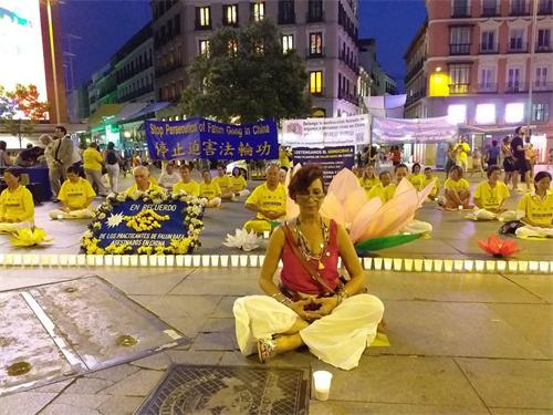 'Figura 3: el 19 de julio de 22019, en la Plaza del Callao de Madrid, la Sra. Vivian Acosta y las practicantes de Falun Gong se sentaron juntas en el suelo y en la vigilia con velas.  '