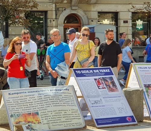 '图13~15:过往民众与游客观看法轮功真相展板'