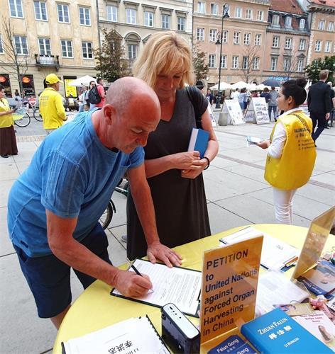 '图16:购买《转法轮》的波兰夫妇在请愿书上签名,反对中共迫害法轮功'