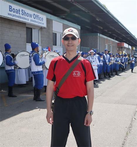 '图9:在密西沙加,当天国乐团在游行前排练时,国伟一直在旁边欣赏他们的演奏。'