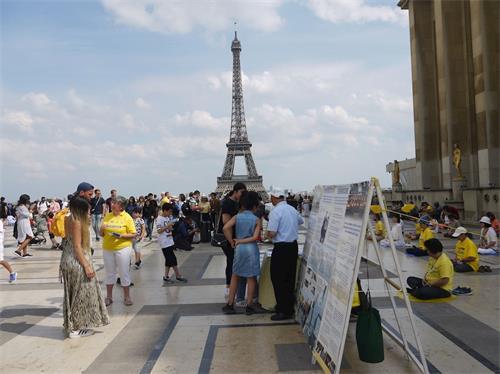 '图1:二零一九年七月七日下午,法轮功学员在巴黎铁塔边的人权广场,进行了法轮功功法演示、讲真相、揭露中共迫害罪行及征集签名反迫害的活动。'