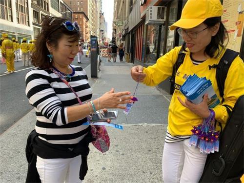 '图4:韩裔民众很高兴接过法轮功学员赠送的小莲花。'