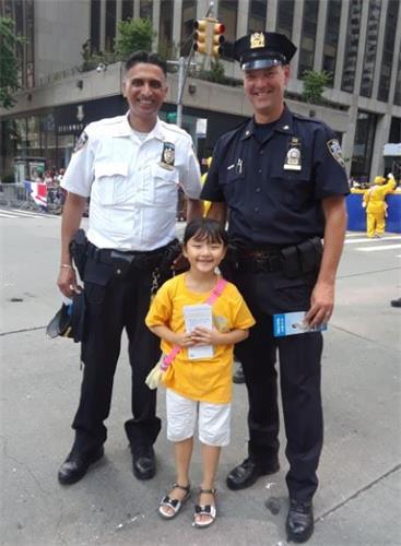 '图5:维护治安的警察接过法轮功小弟子发给的传单,并高兴地与之合影。'