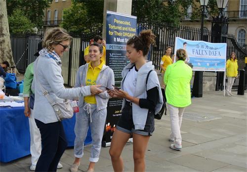 图1:英国学员卡琳娜‧德珀利安(Carina Depelean,中)在跟游客讲述法轮功的真相。