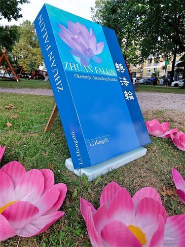 '图1:克罗地亚学员在活动中展示克罗地亚语《转法轮》书模型。'