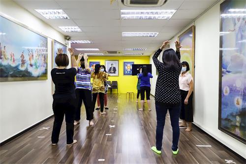 '图1:华语班的新学员学习法轮功<span class='voca' kid='86'>功法</span>动作。'