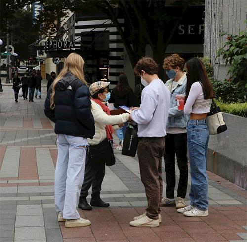 '图10:学员向路人讲真相,一组民众驻足集体签名'