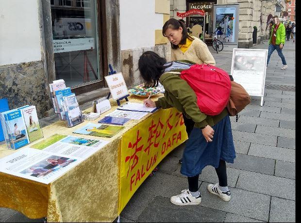 '图5:一位来自台湾了解真相的女士来到展位前签字并表达她对法轮功的支持'