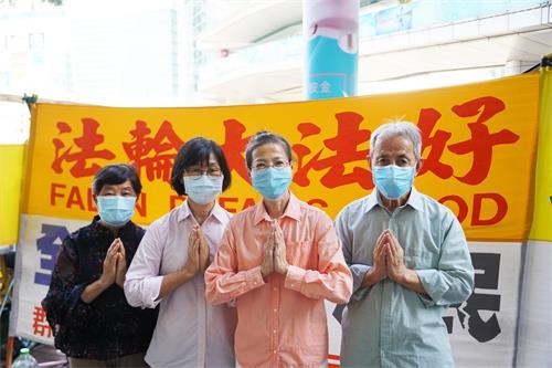 图:香港<span class='voca' kid='62'>真相</span>景点讲真相法轮功学员感恩法轮功创始人李洪志先生洪传大法(左一为郑小姐,左三为小王)。