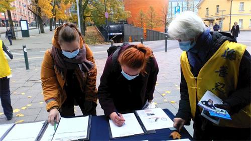 '图1~2:芬兰市民支持法轮功,签名谴责中共暴行。'