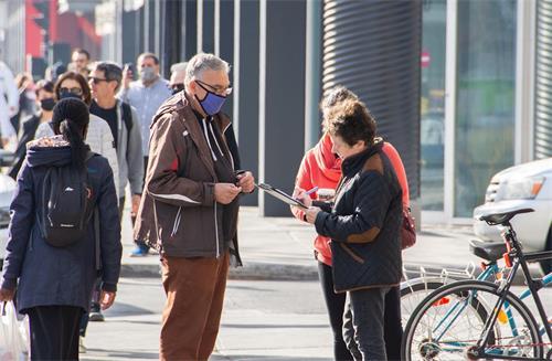'图12~13:法轮功学员在途中向民众征签。'